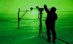 A scientist adjusts instruments in the Arctic in an eerie green light